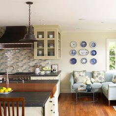Unite adjacent areas to the kitchen by repeating a color or motif. An L-shape sofa in this sitting nook just off the kitchen picks up the blue from the kitchen's tile backsplash./