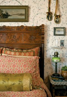 In the master bedroom, airy with a floral paper, silk pillows sit on the Eastlake-style, spoon-carved walnut bed.