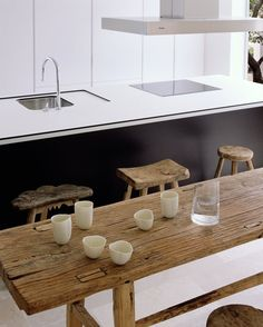 rustic wooden table and variety of rustic stools in the kitchen- CASA DEL PICO  MADRID / SPAIN / 2007 by Abaton Arquitectura