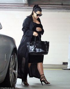 Not on show: Kim Kardashian covers up her figure in all-black outfit and long coat after a...
