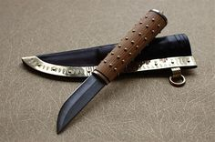 Dark brown leather sheath with polished brass fittings, copper inlays and stamped pattern. Handle in ash with brass rivets, draw ring and brass bolsters. Polar blade. - Nordiska Knivar