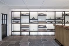 Presentation space featuring glass racks, stone floor and solid wood counter in the Monkey 47 distillery by PHILIPP MAINZER in Loßburg, Germany Photo: Ingmar Kurth Best Interior Design Blogs, Top Interior Designers, Commercial Interior Design, Minimalist Furniture, Facade Design, Shop Interiors, Stone Flooring, Design Awards, Design Trends