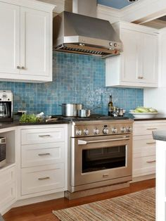 Kitchen | Watery blue backsplash tiles, white cabinets, and stainless appliances