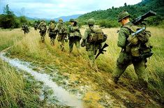 "Walking the high-ground that outlines rice paddies, members of the 1/12th, 1st Brigade, 1st Cavalry go through the paces of a search and destroy maneuver. The U.S. troops were participating in ""Operation Thayer II,"" which took place in North Qui Nhon, South Vietnam."