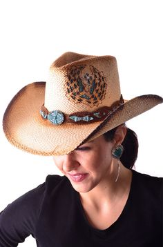 b2015ab515 A Natural color straw hat decorated with turquoise cutouts on the side and  a beautiful hatband