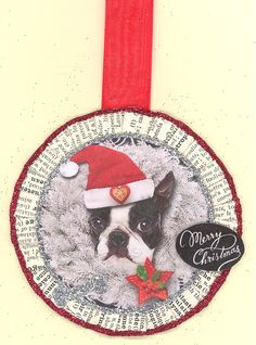 """Boston Terrier. Measures approx. 3 inches in diameter without the ribbon hanger which is about 1.5"""".  On the backside of the ornament there is a painted wooden circle that is signed and dated by the artist. The rosette is folded by hand and is made from papers from a 1932 French Dictionary, the edges are glittered with ArtGlitter.   Hang on a wreath, package, garland, door, tree or light. Comes packaged in a cello sleeve, suitable for gift giving and shipped in a padded envelope."""