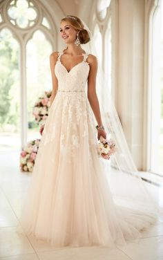 Beaded lace makes up the fitted bodice of this A-line wedding gown from Stella York. The tulle skirt boasts embroidered lace just below the detachable Diamante-beaded belt. The lace illusion back features a zipper hidden under fabric-covered buttons.