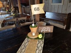 farm table with lace runner burlap and artificial grass square wood slice tennis ball flower pot with flag