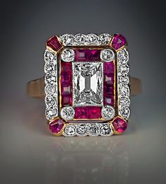 An Early Art Deco Diamond and Ruby Ring circa 1910 Marked with French owl control hallmark and Russian 1908-1917 import mark for 56 zolotnik (14K gold), St. Petersburg assay office. This gold Belle Epoque ladies ring is centered with a rectangular mixed cut diamond (approximately 0.78 ct)  set in a milgrain setting within a double frame of calibre cut rubies and rose cut diamonds. The corners of the ruby frame are highlighted with four diamonds,