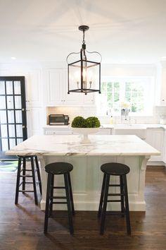 all white kitchen, black bar stools, lantern, black door frame