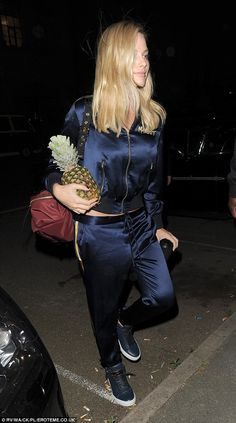 Fruity! Blonde beauty Margot Robbie was seen carrying a pineapple to Cara Delevingne's bir...