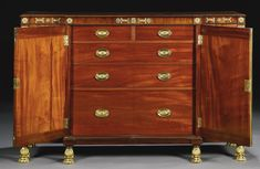 A Regency ormolu-mounted and brass inlaid mahogany breakfront side cabinet, circa 1810, in the manner of George Smith of breakfront outline with ormolu mounted frieze above a pair of central panelled doors fitted with two short and three long drawers flanked by deep drawers with dished fronts inset with massive ormolu lion masks over further cupboards on ormolu paw feet