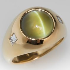 The ring is centered with a round cat's eye chrysoberyl cabochon in a flush setting.