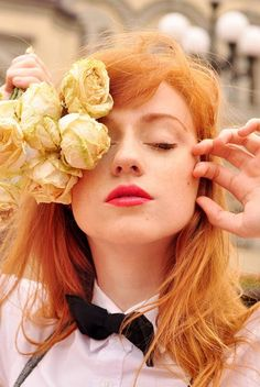 beautiful woman with red hair holding white roses