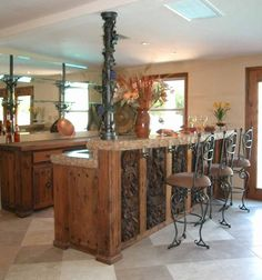 Traditional style white and beige interior color theme decorating of kitchen bar ideas with unique style kitchen island design ideas that have three black metal stools that have round shaped seat cushions also simple base kitchen cabinet design that have storage drawer space design inspirations also beautiful flower plant in the vase for interior kitchen decoration ornament