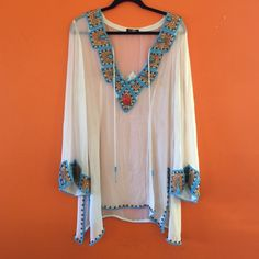 Stunning Turquoise Beaded Tunic Stunning Turquoise Beaded Tunic. Embellishments on the collar, sleeves, back and bottom lining. Perfect to wear by the pool or at an outdoor summer party. Tops Tunics