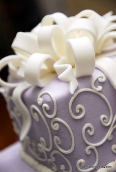 Lavender wedding cake with cream white swirls and ribbon as topper