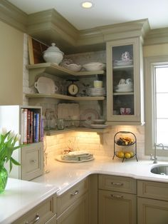 Green painted cabinets, white countertops, white subway title backsplash.                                                                                                                                                                                 More