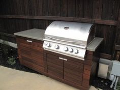 A simple outdoor bbq is accented with a custom concrete countertop and wood veneer siding.