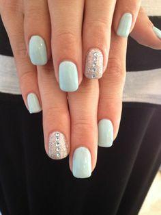Nägel in weichem Blau mit Dekoration aus Glanz und kleinen Kristallen