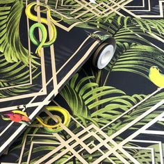 This Congo Geometric wallpaper features tropical birds, animals and palm leaves on a matte black background overlaid with a geometric trellis in metallic gold Geometric Wallpaper Black, Metallic Wallpaper, Black Wallpaper, Paper Wallpaper, Vinyl Wallpaper, Wallpaper Roll, Matte Black Background, Tropical Animals, Animal Print Wallpaper