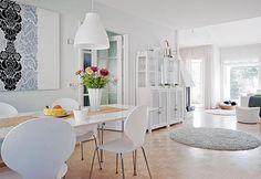 Avoimen ja valoisan ruokailutilan seinällä on Marimekon Ananas-kankaasta teetetty taulu. | Rennosti rinteessä | Koti ja keittiö | Riitta Kivilahti | Kuva Jeppe Tuomainen