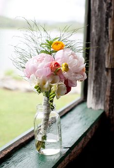 """Brides.com: A Summer Camp-Themed Wedding in NH. The bride's sister, Emma, """"and I carried matching bouquets we arranged ourselves with sprigs of mint, yellow and peach ranunculus, white freesia and pink peonies,"""" Ariel says."""