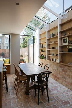 A wall of storage filled with art and ceramics features inside this house that architect Neil Dusheiko has renovated for his father-in-law, near his own home in north London.