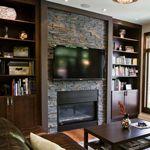 Living room TV and fireplace wall clad in ErthCOVERINGS Springwood Black Ledgestone Series natural stone veneer