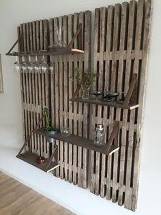 DIY hygge i køkkenet. Gamle treller fra byggepladsen bruges her som vægophæng til hylder ophængt med lædderstropper. Ved at anvende en gammel palderamme til hylderne får de samme farve som træet i trellerne.