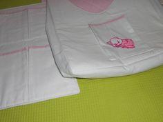 """Kit porta fraldas para pendurar em varão. Bolsão porta fraldas e porta objetos com 6 bolsos.   Bolsão em tecido de algodão branco com a parte das costas em xadrez rosa e branco quiltado. Abertura em """"U""""  e bolsinha com aplicação de bebê urso dormindo. Porta objetos com 6 bolsos com acabamento em xadrez rosa e branco. Diaper pocket organizer."""