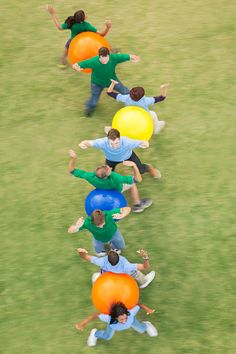 Stock Photo : Teammates performing fitness ball team building activity