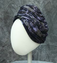 Turban of purples, blue, and green jersey knit in a camouflage pattern by Roth Margit & Helen Clarke, c.1960.