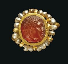 A BYZANTINE GOLD AND PEARL RING   CIRCA 5TH-6TH CENTURY A.D.   The hoop of hemi-spherical section, the high circular bezel with 18 pearls strung with gold wire around the edge, with later carnelian cameo with profile male head facing right  1 in. (2.5 cm.) wide
