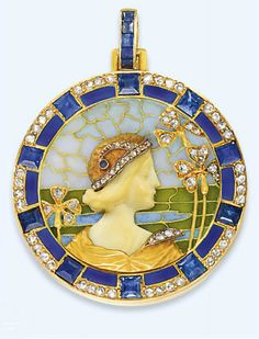 AN ART NOUVEAU GEM-SET ENAMEL PENDANT, BY LUIS MASRIERA  Designed as a circular-shaped plaque centring upon a carved ivory female profile, the sculpted gold cloak and cap with sapphire and diamond accents, enhanced by a translucent green and blue plique à jour enamel landscape surround with diamond-set floral detail, to the blue enamel, sapphire and rose-cut diamond frame, with sapphire-set suspension loop, mounted in gold, circa 1910, diameter 4.1cm wide  Signed Masriera Hs