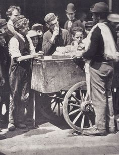 """Children crowd around an Italian ice-cream seller and his cart. The image is taken from the book, 'Street Life in London' (1877), with text written by John Thomson and the journalist Adolphe Smith. In America they were called """"The Hokey-Pokey Man""""."""