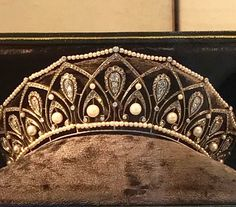 A BELLE EPOQUE NATURAL PEARL AND DIAMOND TIARA Designed as a graduated series of rose-cut diamond palmette motifs, each with old-cut diamond drop shaped centre highlights and natural pearl accents, between further natural pearl line borders, circa 1910, French import marks for silver and gold, maximum height 4.7cm