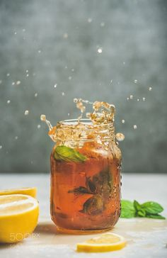 Iced tea with bergamot lemon mint in jar with splashes by 2enroute