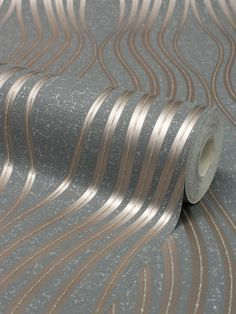 This beautiful Quartz Wave Wallpaper will add a stylish finishing touch to most rooms of your home. The design features an elegant curved pattern of wavy lines with a metallic copper finish and glitter detailing. This is set on a matte paper in a slate grey tone that is infused with glitter particles and has a textured fabric effect finish. This high quality vinyl wallpaper could be used to create a feature wall or to decorate an entire room. Waves Wallpaper, Vinyl Wallpaper, Crushed Velvet Wallpaper, Metallic Wallpaper, Pattern Matching, Wave Design, Designer Wallpaper, Slate, Door Handles