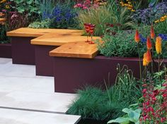 Gartenbank aus Holz auf Roststützen an einem blumigen Hochbeet