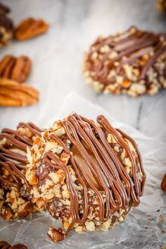 These turtle thumbprint cookies are amazing! Rich chocolate cookies rolled in chopped pecans, topped with salted caramel sauce and drizzled in chocolate!
