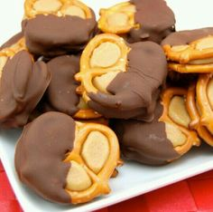 """Peanut Butter """"Buckeye"""" Pretzel Bites:  1 cup of creamy peanut butter 3/4 cup of brown sugar 2 Tbs of softened butter 1/2 cup of powered sugar Miniature pretzels 1 bag of chocolate chips or Merkins chocolate wafers Line a baking sheet with wax paper and set aside. In a mixing bowl, beat peanut butter and butter until combined. Add sugars and mix well. You should be able to roll mixture into small balls without sticking to your hands. If needed, add more powered sugar until it easy to roll…"""