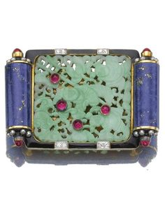 Attractive gem-set buckle/ brooch, Cartier, 1928. Centring on a carved and pierced jade plaque within a lapis lazuli and black enamel border, highlighted with cabochon rubies, rose and single-cut diamonds, belt loops, additional detachable brooch fitting, French assay and maker's marks, numbered, signed Cartier.
