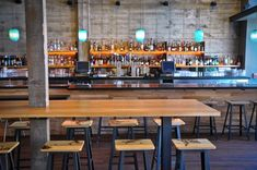 Custom iron stools by Ferrous Studios in Richmond, CA, feature designs created with a branding iron by American sculptor John Bisbee. Amber LED strips illuminate the bar shelving