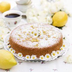 Enkel citronkaka garnerad med florsocker, rivet citronskal och söta små tusenskönor.