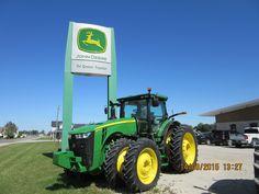 John Deere 8370R beneath Tri Green Tractor sign
