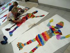 Kindergarten students are beginning the year by learning about different types of lines and the emotional qualities associated with them. After practicing making different types of marks in their sketchbooks, students filled in a life size outline of their bodies with as many different types of lines as they could think of. The kids are in the process of painting their projects with tempera cakes.