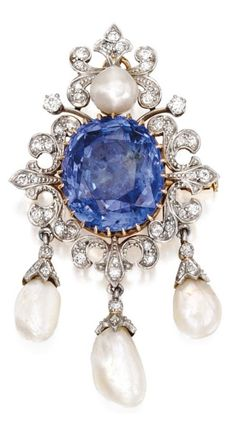 An Antique Platinum, Gold, Sapphire, Diamond and Pearl Pendant-Brooch, Circa 1900. Centring an oval-shaped sapphire weighing 22.24 carats, framed by scrollwork flourishes set with old mine and old European-cut diamonds, accented by four variously-shaped pearls.