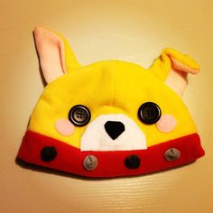 An dog beanie/plushy hat! One of its ear is flopped over, and it's made out of soft, kind of stretchy polar fleece! The muzzle, blush marks, studs on its collar, and nose are made out of felt, and is securely hot glued on. The eyes are black buttons, and are also securely affixed with hot glue.  ...