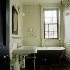 claw foot bathtub, worn chocolate hardwood